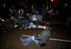 Protesters fall on the ground as they are chased by riot police during a demonstration against high electricity prices in Sofia