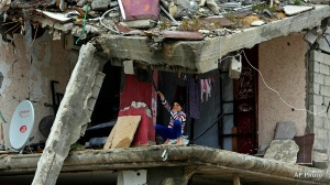 A Palestinian girl sits inside a room of her family's building which was damaged in last summer's Israel-Hamas war, in the Shijaiyah neighborhood of Gaza City, northern Gaza Strip, Monday, Feb. 23, 2015. (AP Photo/Adel Hana)